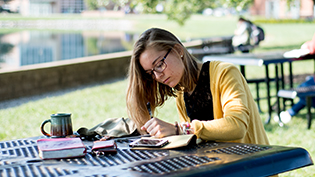 Female student does homework on a picnic table