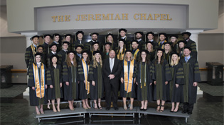 """Group of students in cap and gown on risers in front of the """"Jeremiah Chapel"""""""