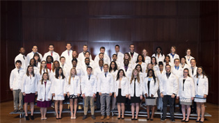 A group of students in white (pharmacy) coats in a group picture on stage