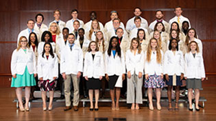 Group photo of new Pharmacy students all wearing white lab coats.
