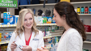 Pharmacist talking with a patient over a counter.