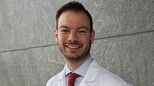 Male student dressed in a white lab coat standing outside in front of a stone wall.