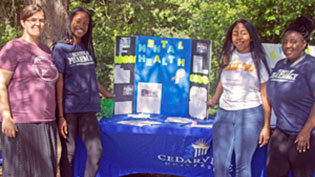 Students promoting mental health next to a table filled with related brochures.