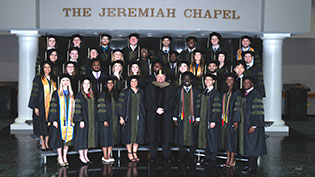 Group photo of students dressed in commencement caps and gowns.