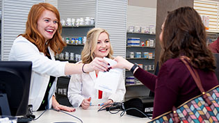 Female pharmacist handing a bag over the counter to a customer.