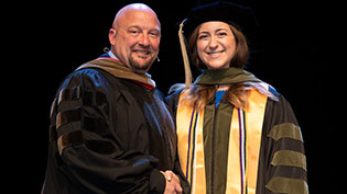 Commencement photo of student being congratulated by the director of the pharmacy program.