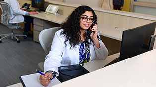 Female Pharmacy student dressed in white lab coat at a desk making phone calls to help with contact tracing.