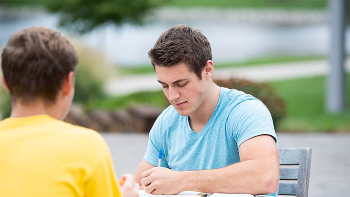 Two students studying at an outdoor table.