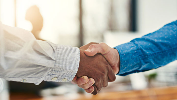 two men handshake while in business attire