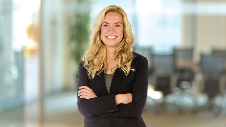 woman smiles at camera with arms crossed in business attire