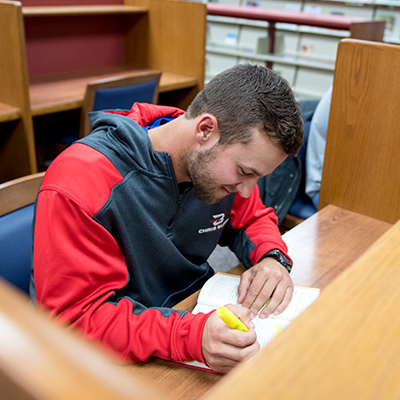Male student studies in library