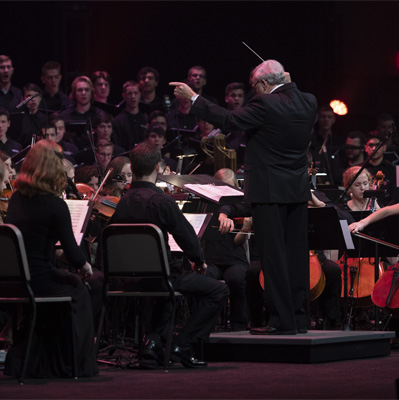 Conducor leads orchestra and choir