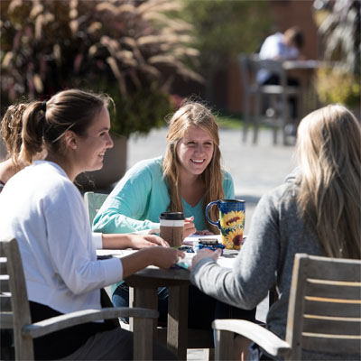 Three female students sitting at a high table outside at Cedarville University