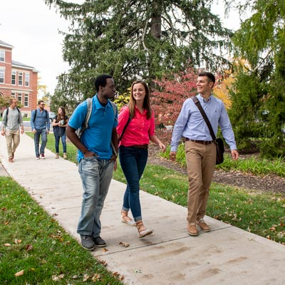 Three diverse students walking on a sidewalk at Cedarville