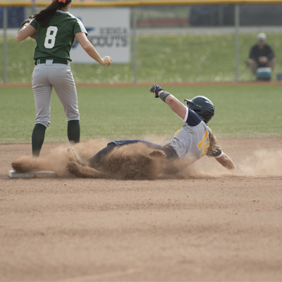 Female softball player sliding to the base with cloud of dust trailing behind and opposing team member running