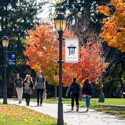 Students walk down a sidewalk in the fall