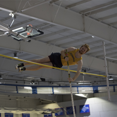 Image of male pole vaulter in mid air over bar